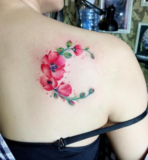 Татуировка на лопатке у девушки узора с маком