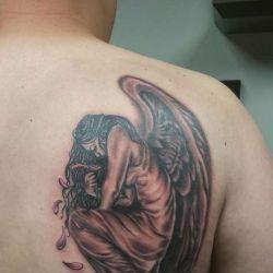 Девушка в виде ангела на лопатке